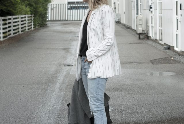 Style: pinstriped blazer and blue jeans.